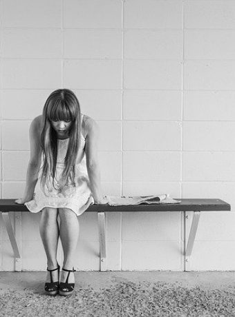 Reliable Ways to Help kids manage their emotions. Image of a girl sat on a bench