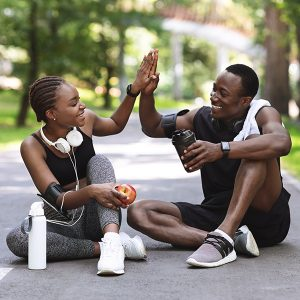 Relationship Goals. Active African Couple High-Fiving To Each Other After Successful Outdoor Training, Resting On Path In Park