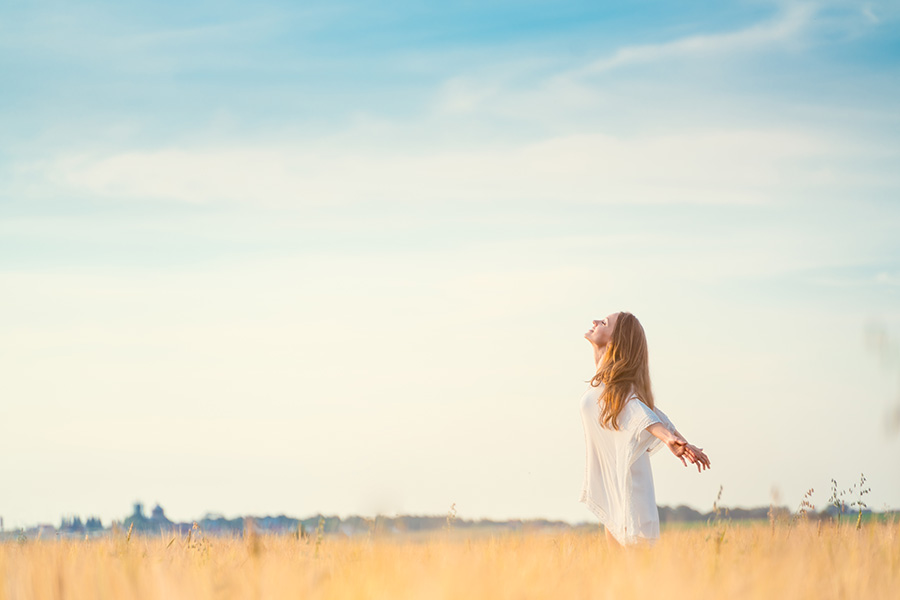 Lady in a field with arms open wide and looking up to the sky