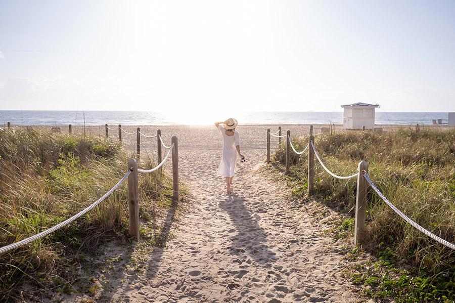 Banishing bad habits image. lady walking on the beach with sun shining